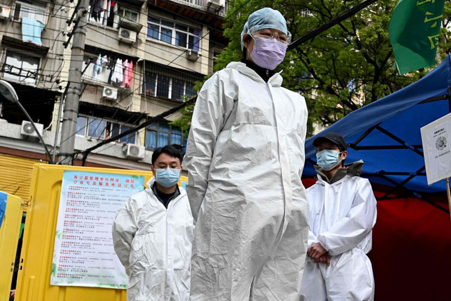 Community volunteers in hazmat suits observing three minutes of silence to mourn those who died in the fight against the Covid-19 pandemic in Wuhan, in central China's Hubei province, last week. Scepticism abounds about the reliability of Chinese off