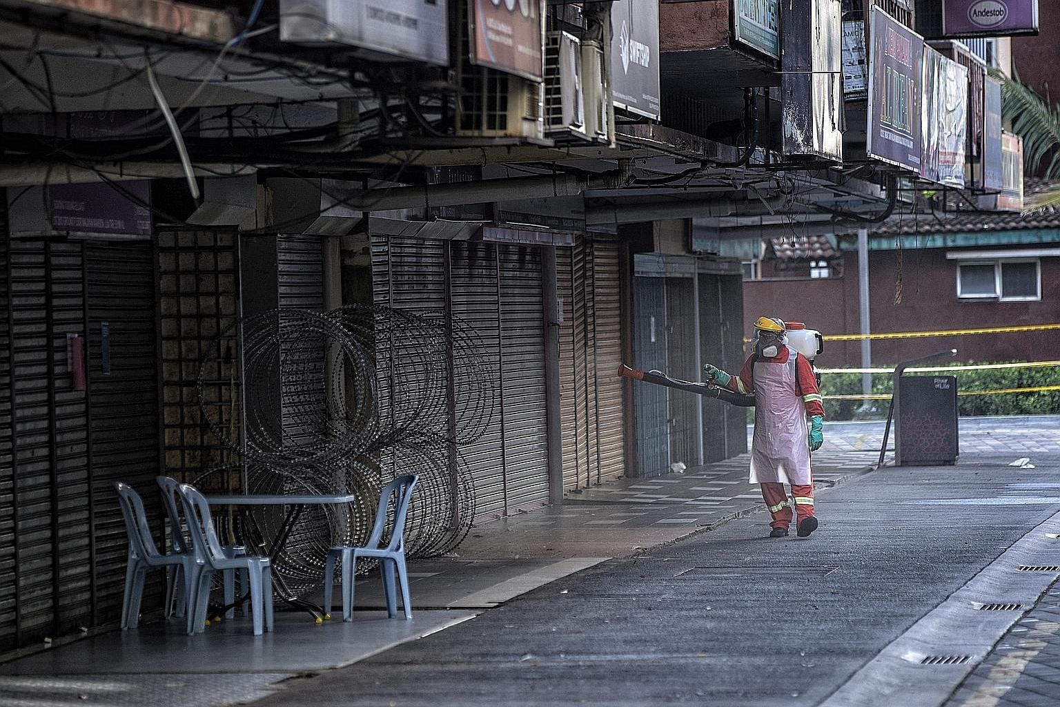 A food delivery rider in Jakarta yesterday. Indonesia's partial lockdown reflects the competing priorities between its central and local governments. A deserted street in Makati, south of Manila, last week. The Philippines has put a third of its coun