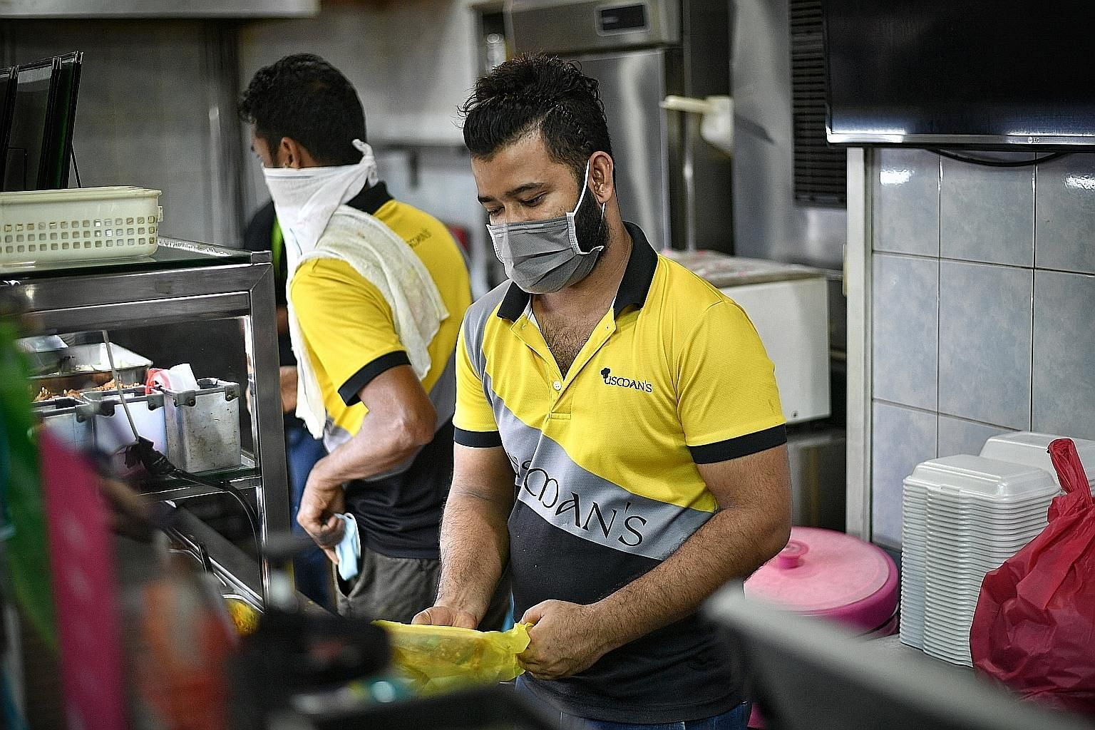 Workers at Usman Restaurant donning masks while preparing food for delivery yesterday. Such facial protective gear is mandatory from today for all workers engaged in the sale and preparation of food and drinks, to safeguard public health and prevent