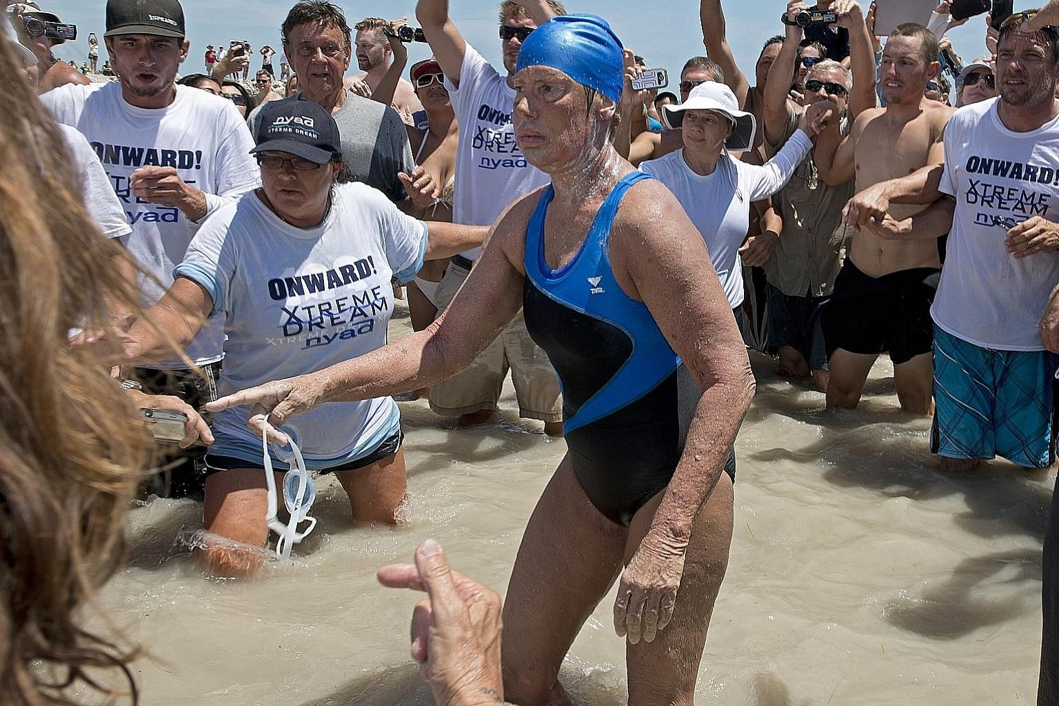 Diana Nyad emerging from the Atlantic Ocean after completing her marathon swim from Cuba to Key West, Florida in 2013 at age 64. PHOTO: AGENCE FRANCE-PRESSE