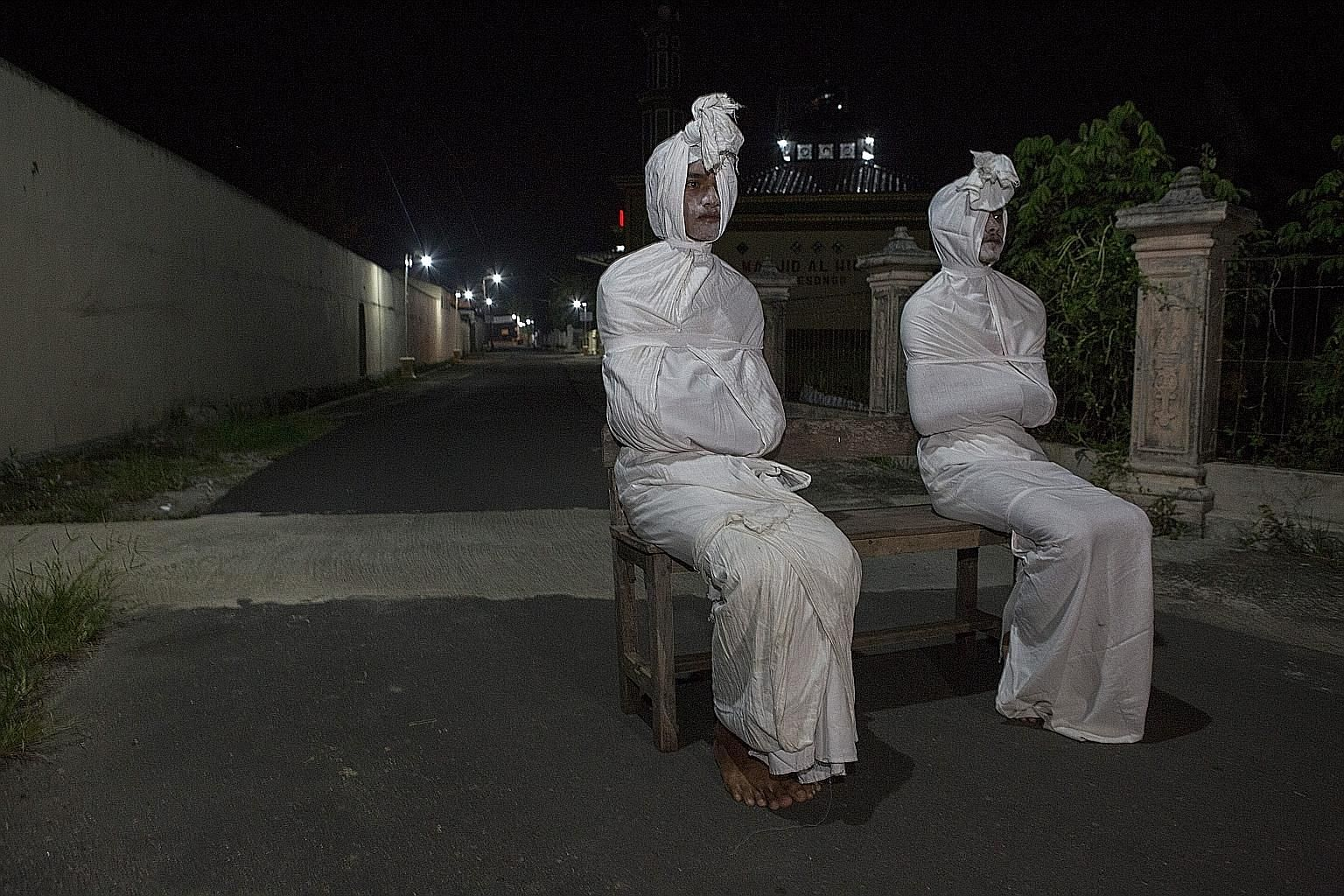 "Volunteers dressed as ""pocong"", or shroud ghosts, in a bid to urge people to stay home amid the coronavirus outbreak in a village in Sukoharjo, Central Java. Indonesia yesterday reported 27 more deaths from the virus, which has now claimed close to 5"