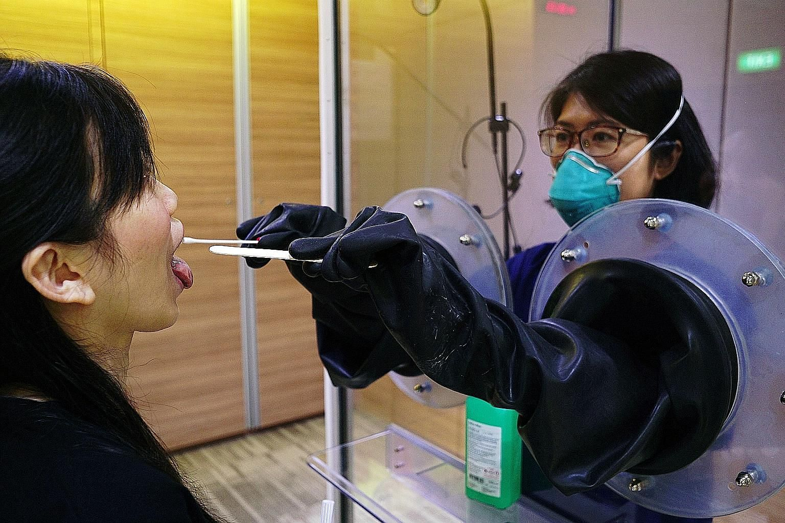 Throat swabs being done with SG Safe (left), a transparent booth system, and SG Shield, which gives healthcare workers added protection. PHOTOS: SGH