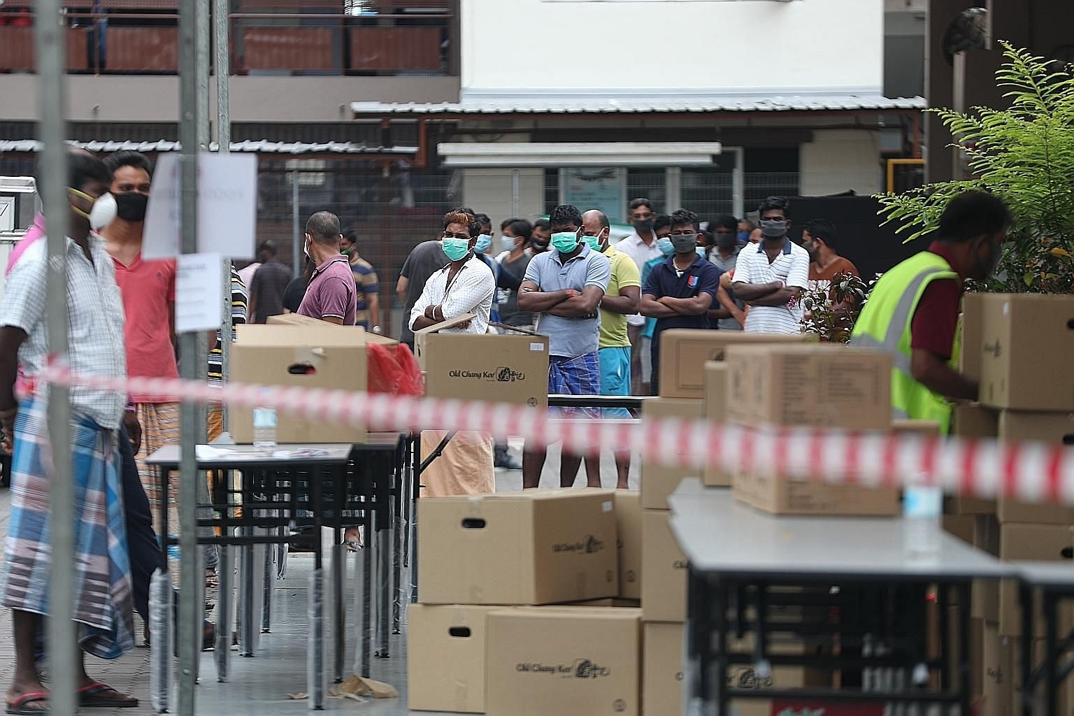 Migrant workers who are residents of Jurong Penjuru Dormitory 1 queueing to collect food yesterday. The dormitory is among those with a cluster of Covid-19 cases. Medical posts are being set up at all 43 purpose-built dormitories and other locations,