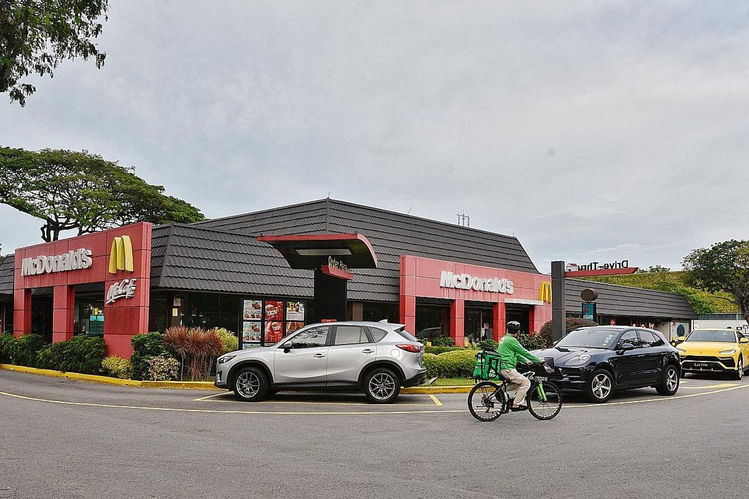 """A line of cars forming outside McDonald's Kallang drive-through outlet yesterday, the first day the fast-food chain stopped offering walk-in takeaways until 11.59pm on May 4. McDonald's Singapore said the precautionary move would help """"flatten the cu"""