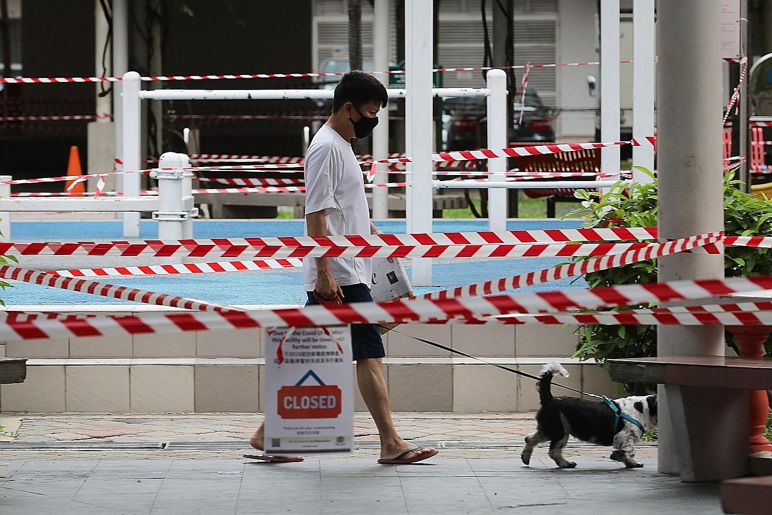 A man walking his dog in Jalan Sultan yesterday. Evidence suggests that workers providing essential services are getting infected.