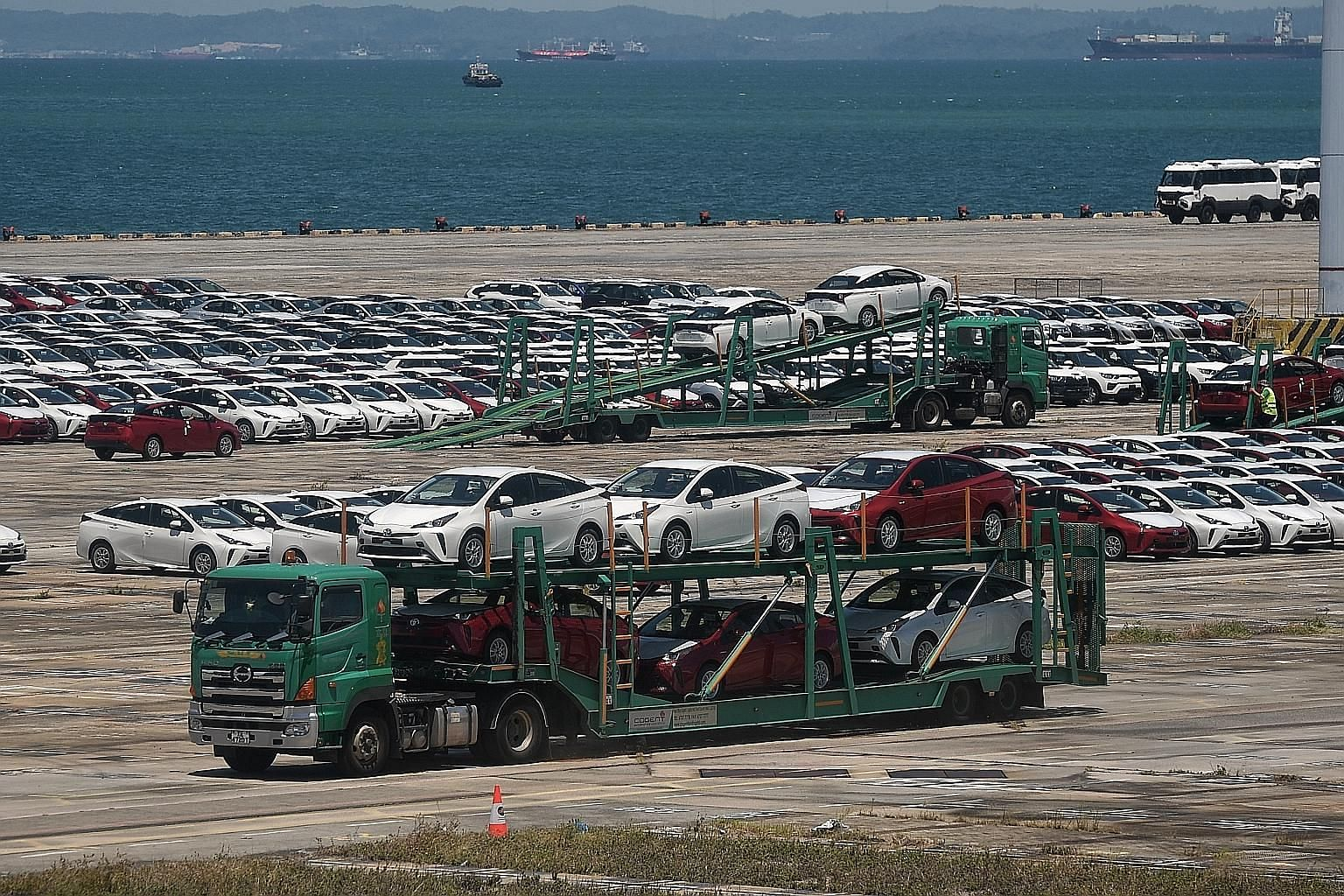 "Rows of cars in Tanjong Pagar Terminal on Monday. A manager at a listed motor firm said: ""Shipments are still coming in. Stock will pile up, and storage space is becoming a big issue."""
