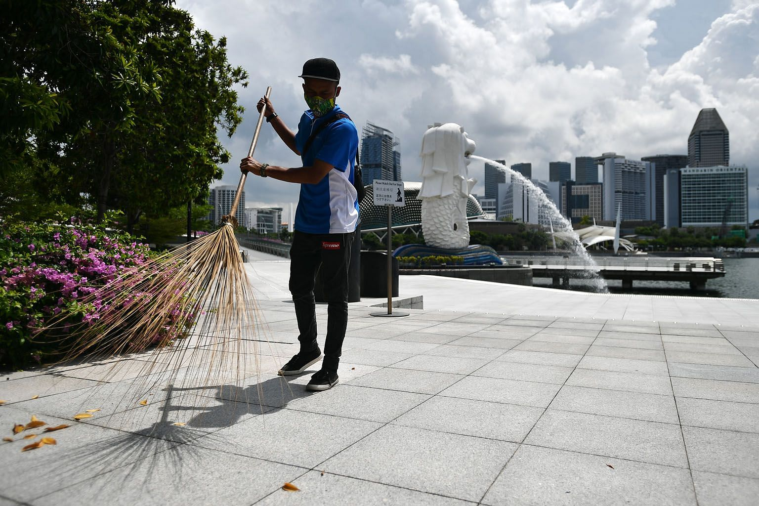 Cleaner Hamedi Hamzan at work at the deserted Merlion Park on Thursday. Visitor arrivals fell by half in February compared with the year before, and the numbers for last month are expected to hit new lows.
