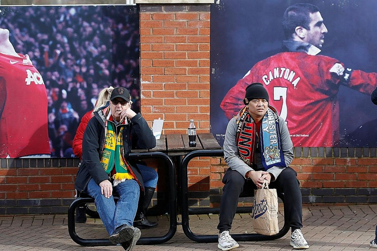 Fans outside Old Trafford before the Manchester United v Manchester City match on March 8. A restarted season behind closed doors will come at a cost to clubs. PHOTO: REUTERS