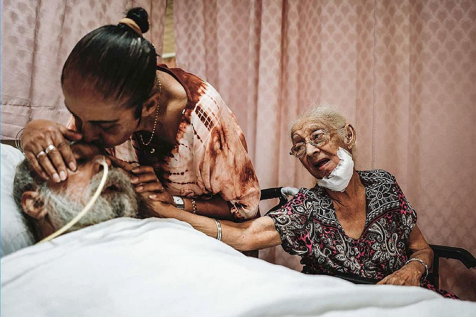 In a photo taken before the circuit breaker began, an HCA Hospice Care patient, Madam Niranjan (at right), and her daughter say goodbye to Madam Niranjan's son before his death. PHOTO: HCA HOSPICE CARE