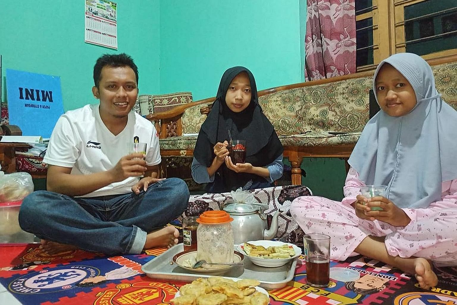 Top: Central Java resident Tri Wicaksono breaking fast with his wife (right) and sister-in-law last Saturday. Because of Covid-19, he has been avoiding crowded places.Above: