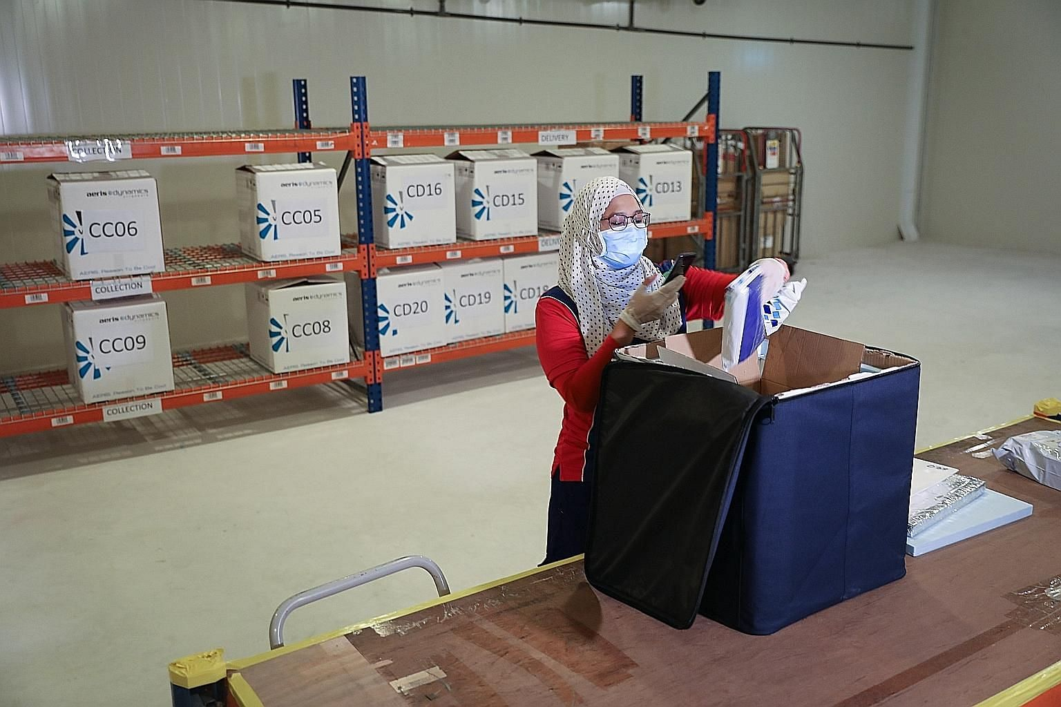 Speedpost courier Ismadiana Samsudin, 37, collecting a cold-chain box for delivery of medications that require refrigeration at SingPost's regional e-commerce logistics hub in Tampines last Friday.