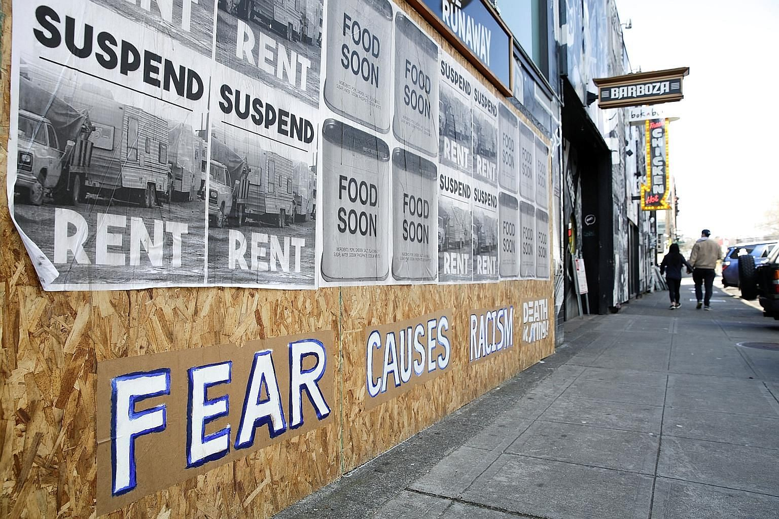 """A sign with the words """"Fear causes racism"""" on a boarded-up business in Seattle's Capitol Hill neighbourhood. Experts have pointed out that throughout history, immigrants and minority communities have been blamed for and attacked during disease outbre"""