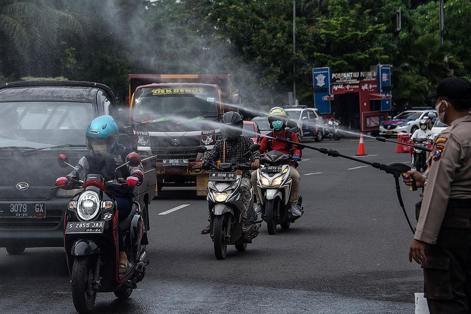 Indonesian policemen spraying disinfectant on motorists at a border checkpoint between Surabaya and its satellite cities to curb the spread of Covid-19 on Tuesday. Indonesia has been in the world spotlight for having the highest fatality rate for Cov