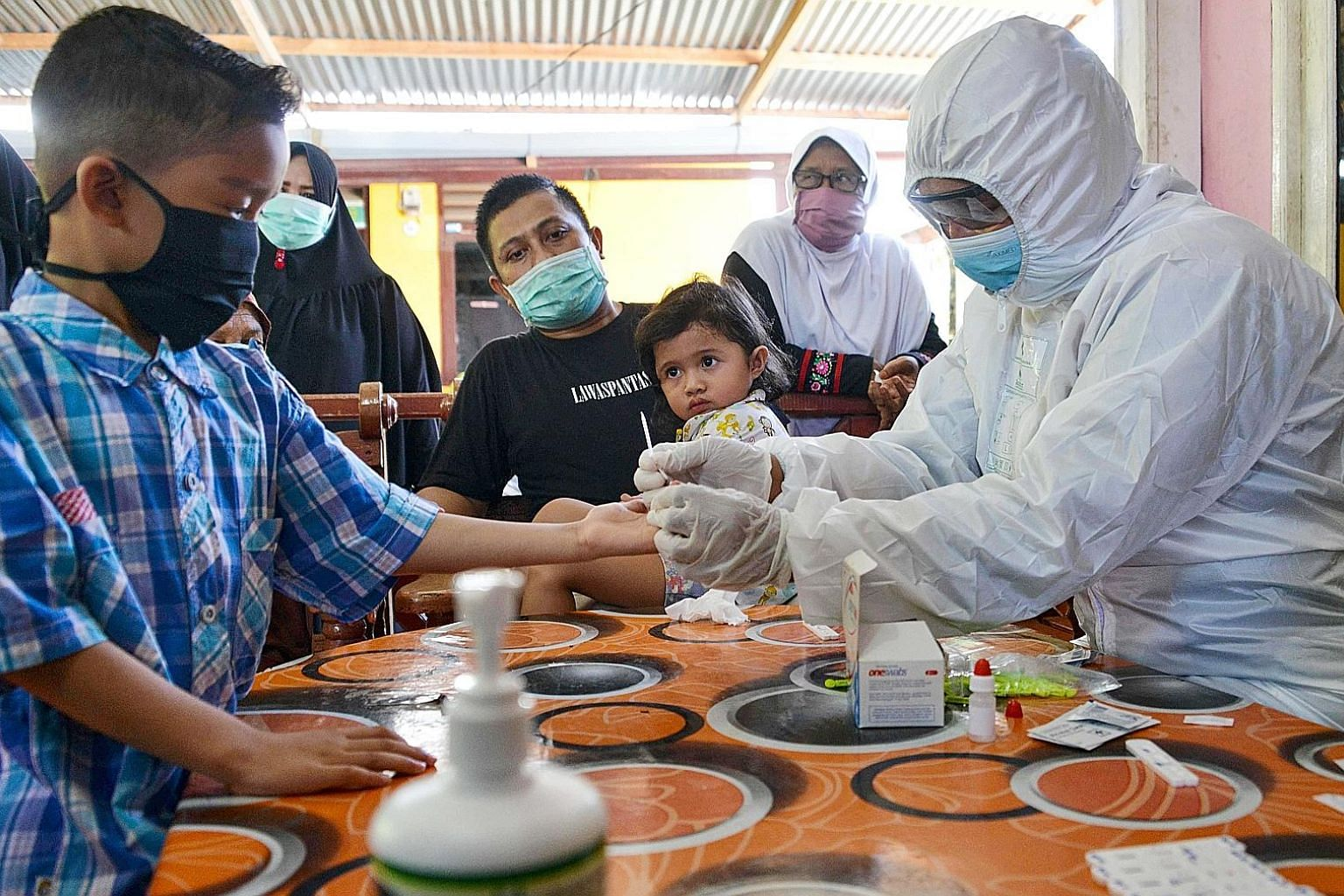 A boy having his blood sample taken as officials conducted Covid-19 testing on Wednesday for residents living close to a boarding house in Banda Aceh where foreign students had reportedly fallen ill. The Indonesian government last week announced a ba