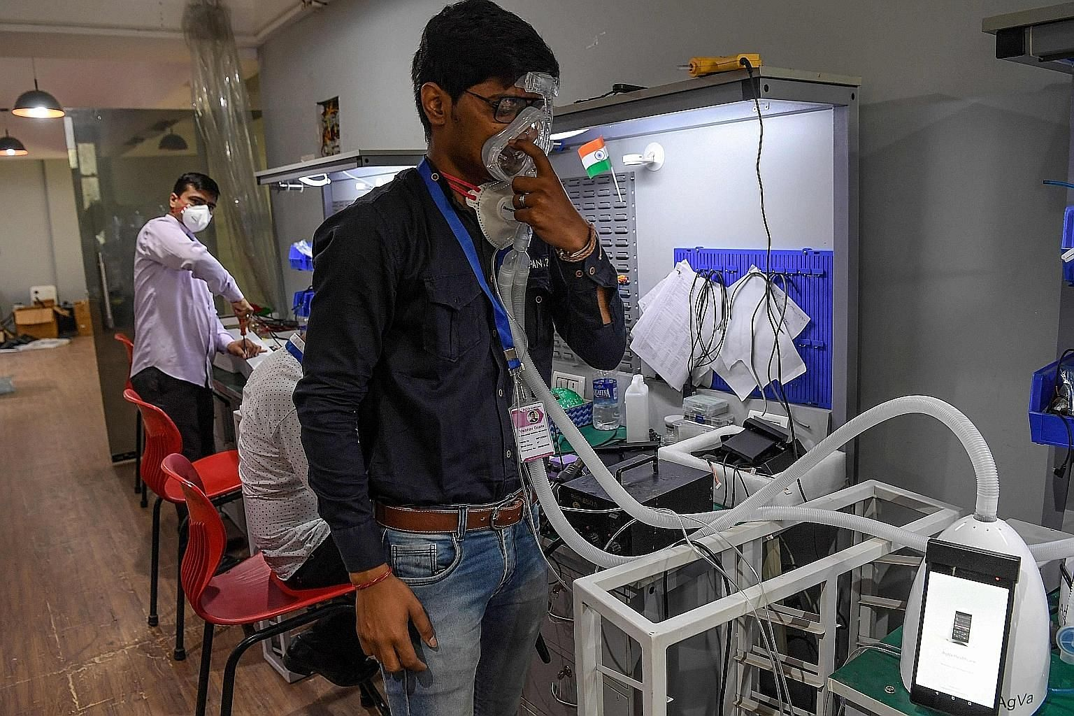 An AgVa Healthcare employee showing how the company's ventilator works, at the research centre in Uttar Pradesh state, in March. The company came up with the toaster-sized ventilator that is priced at less than a fourth of conventional ventilators, a