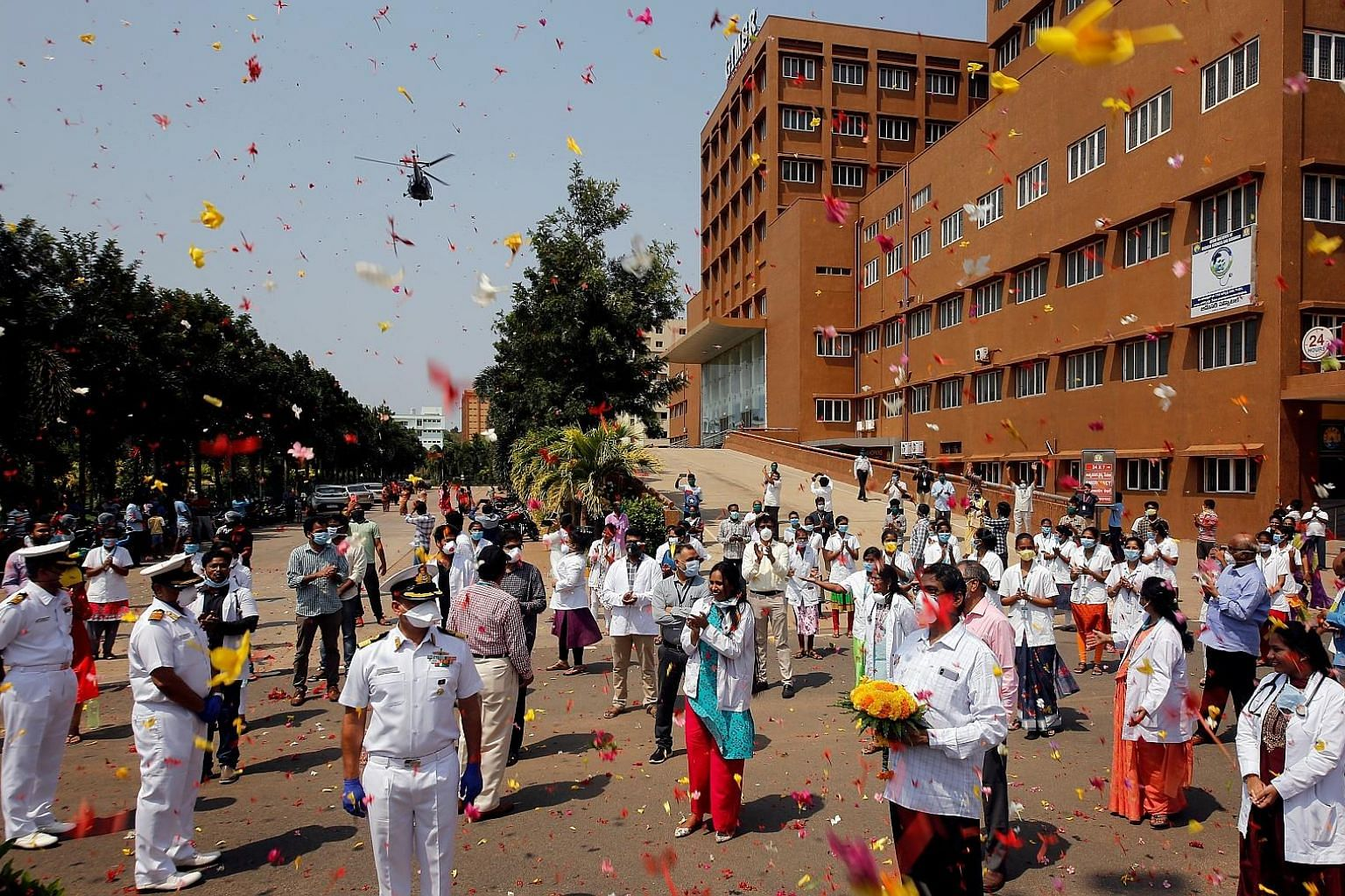 An Indian Navy Chetak helicopter showering flower petals yesterday over the premises of a hospital in Visakhapatnam as part of an event showing gratitude to the front-line warriors fighting the coronavirus outbreak in the country.