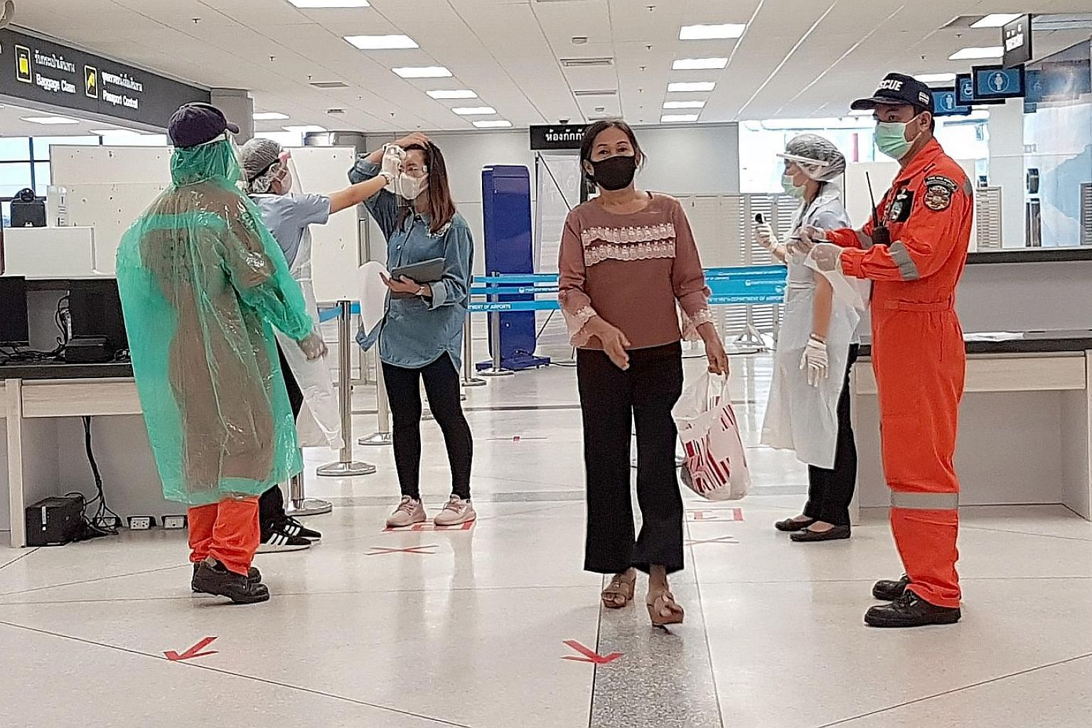 ST reporter Tan Hui Yee on an almost empty flight from the Thai capital Bangkok to the north-eastern province of Ubon Ratchathani. From left: An attendant on the one-hour flight from Bangkok to Ubon Ratchathani wearing disposable plastic overalls on