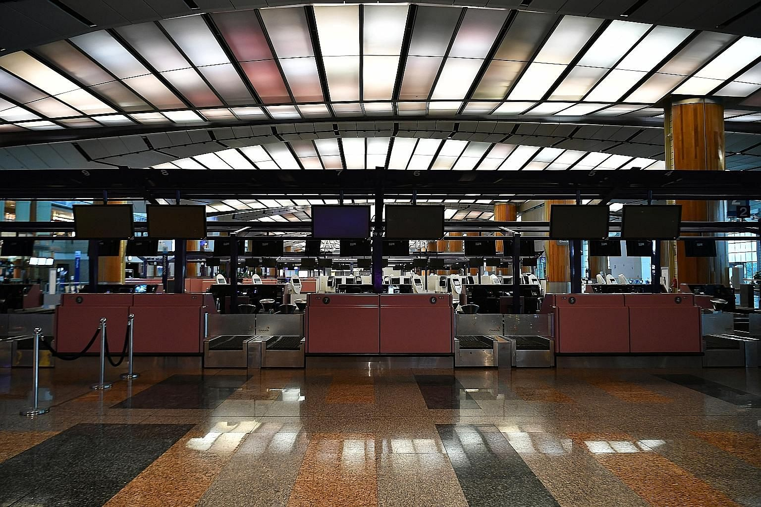 Empty check-in counters at Changi Airport Terminal 2 last week. The number of visitors to Singapore plummeted to about 240,000 in March, the lowest since the Sars outbreak. ST PHOTO: LIM YAOHUI