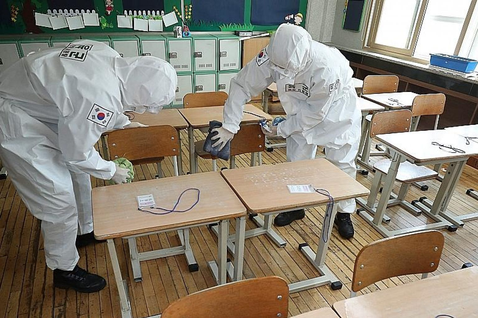 Army personnel disinfecting a classroom at an elementary school in Daegu, South Korea, last Friday. High school seniors will be the first to return to school on May 13, while the rest will follow in phases as schools reopen.
