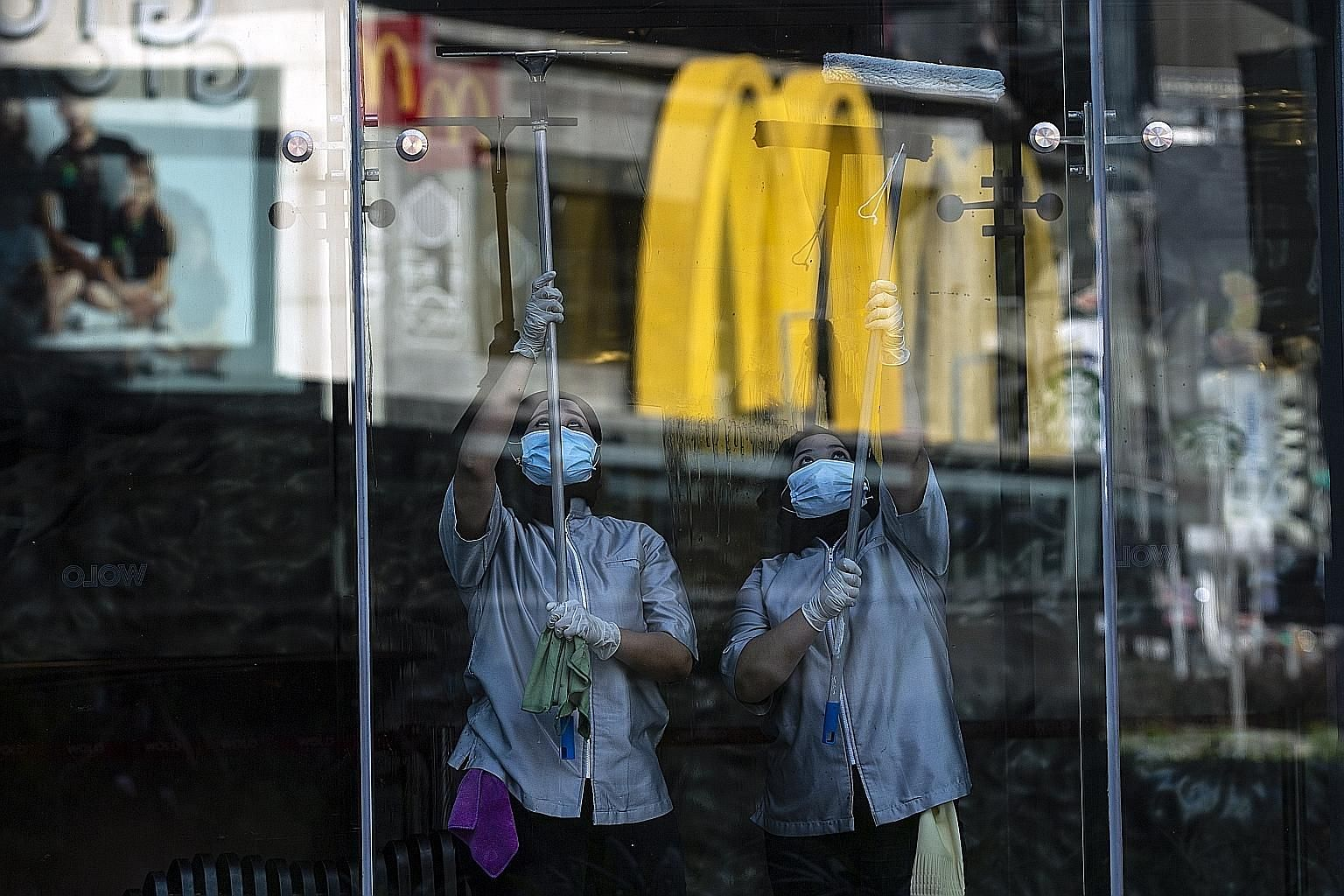 Above: Workers cleaning a shop's glass panel in Kuala Lumpur yesterday, when the Malaysian government allowed certain economic and social activities in the country to resume after 47 days of a movement control order. Right: Seats in a train marked ou