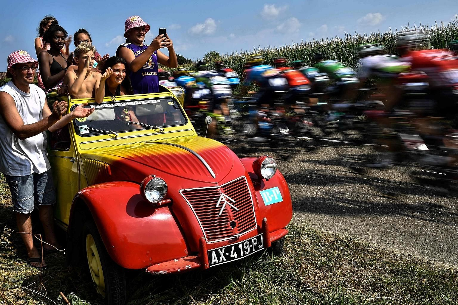 Fans lining the Tour de France route to cheer the peloton on, such as in this 2018 photo, is an enduring image of the event. PHOTO: AGENCE FRANCE-PRESSE