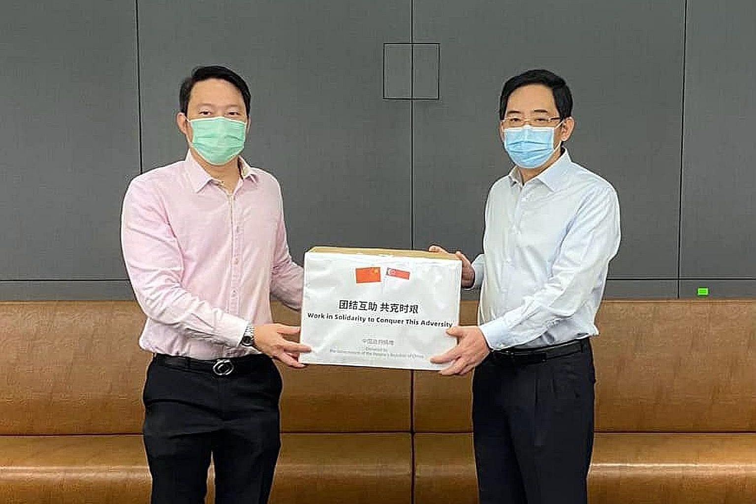 Senior Minister of State for Health Lam Pin Min (left) receiving a donation of masks from China's Ambassador to Singapore Hong Xiaoyong at the Ministry of Health yesterday.