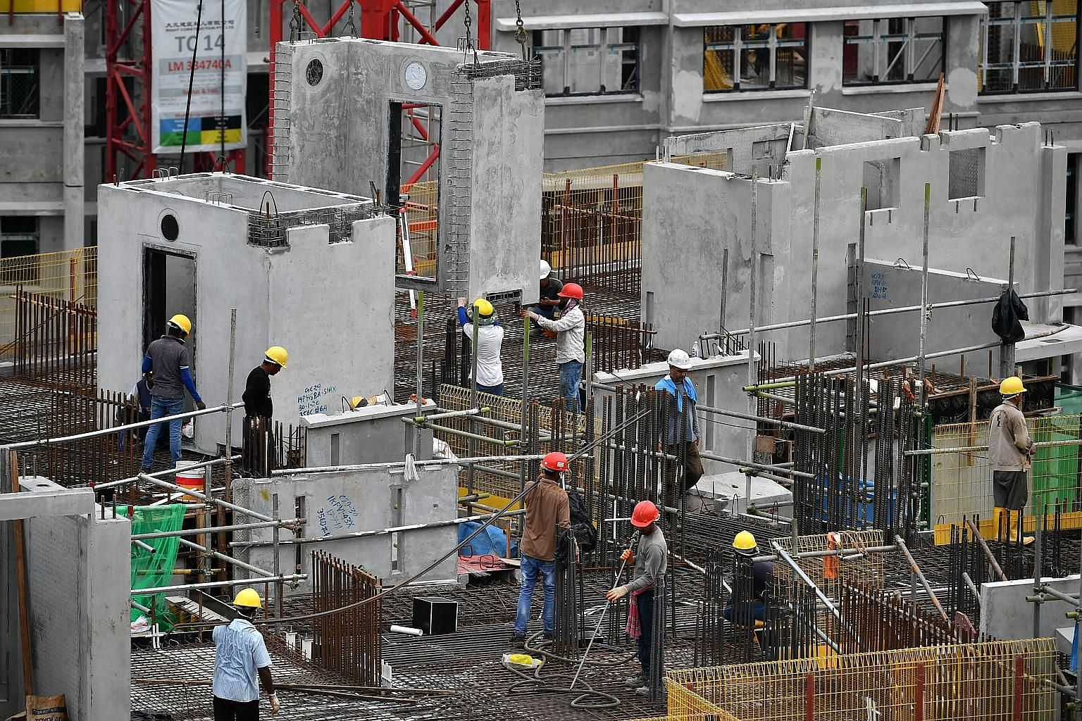 Workers at the construction site for HDB's Ubi Grove project. Covid-19 has made clear that a fundamental review is needed of the desired outcomes of economic and other activities as well as full costing of foreign labour. These will bring the numbers