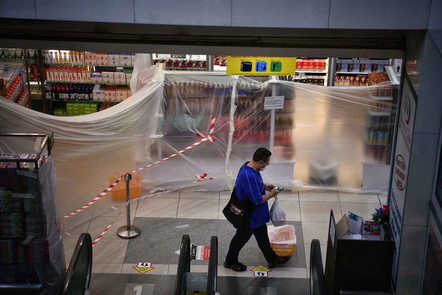 Above: Out-of-bounds sections inside Mustafa Centre have been sealed off with plastic sheets and unused escalators are blocked with red cordon tape. Left: Shoppers and staff at Mustafa Centre yesterday. Only the supermarket section of the mall in Lit