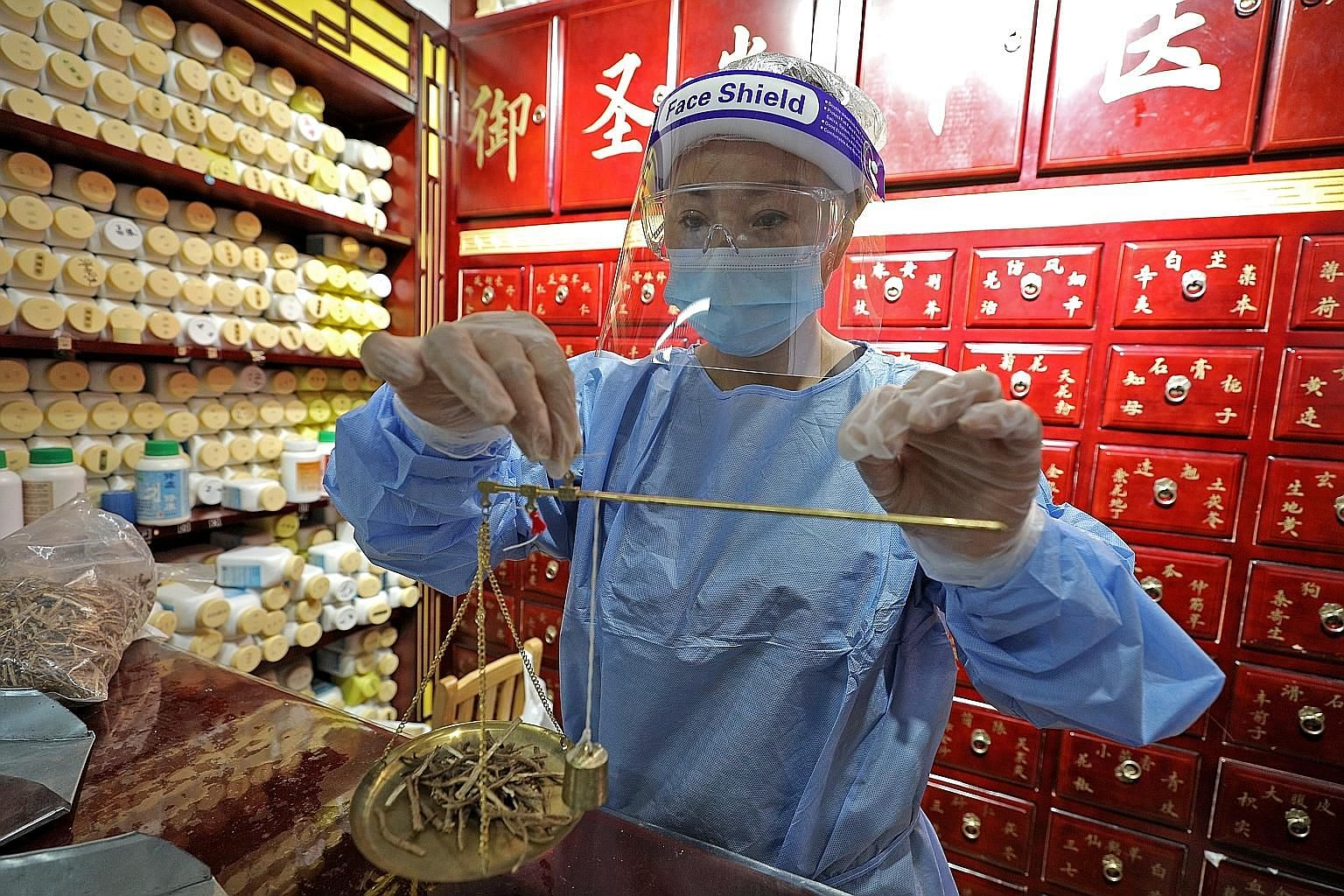 Physician Li Huarong preparing Chinese herbs for her patients on Tuesday, the first day that 130 medical halls attached to registered TCM practitioners could resume treatments and services since the start of circuit breaker measures.