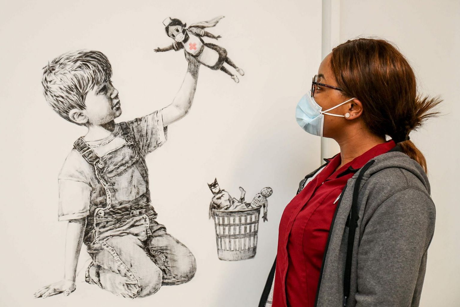 Banksy's new artwork Game Changer shows a boy playing with a nurse superhero toy, with figures of Batman and Spiderman discarded in a basket.