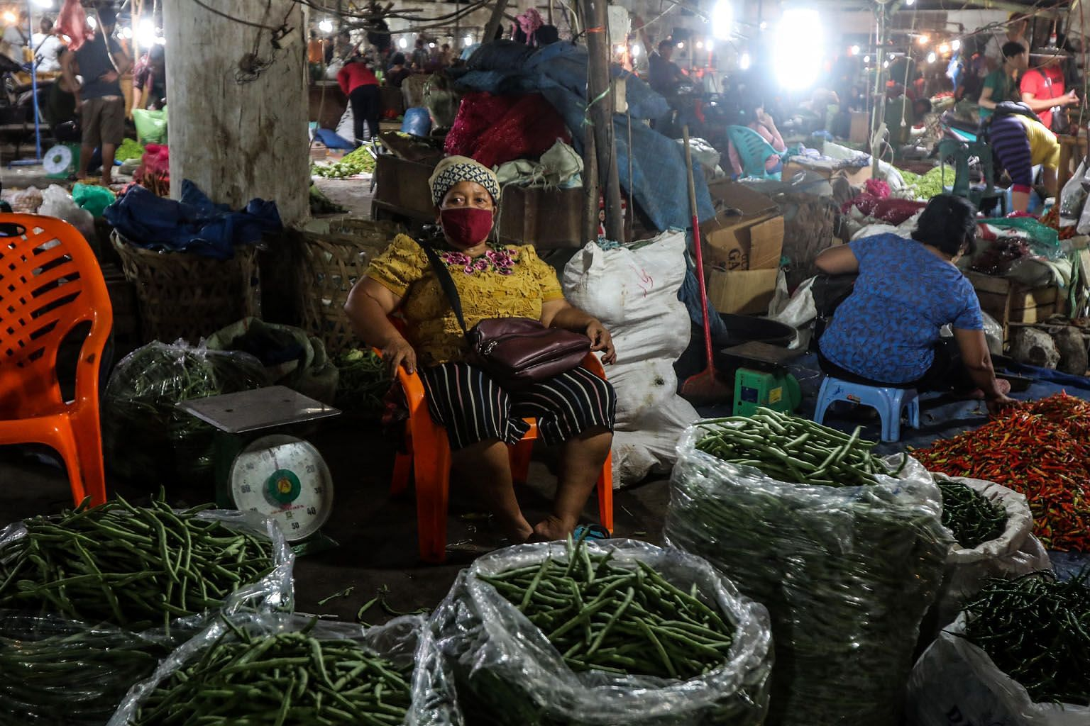 A vegetable vendor waiting for customers on Thursday at a market in Medan in Indonesia's North Sumatra province, as businesses struggle to survive amid strict social distancing rules.