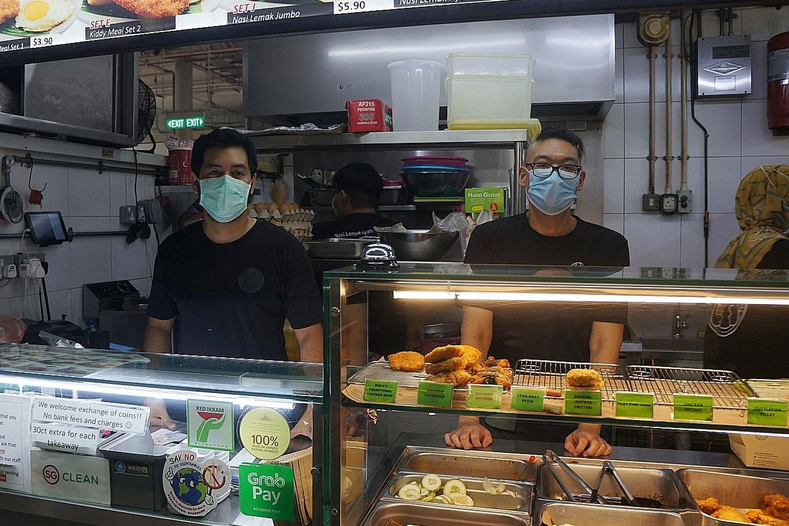 Mr Patrick Foo (right) is grateful for the stability that the work at Mr Noorman Mubarak's nasi lemak stall provides. He said his salary is enough for him to survive on and help should be offered to others in need.