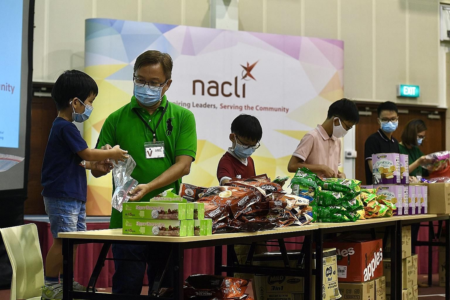 Singaporean Joshua Koh, 47, packing items with his youngest son Joash (far left), three, alongside sons Jireh, 10; Jakin, 13; and Jedidah, 17; and his wife Mrs Koh, 44, last month at the National Community Leadership Institute (Nacli) in South Buona