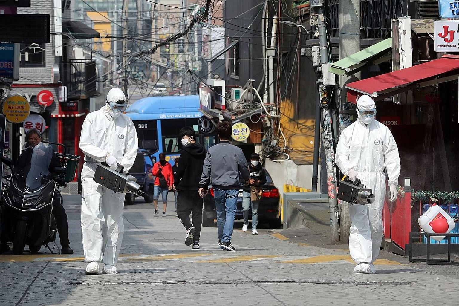 Workers spraying disinfectant in Seoul's Itaewon neighbourhood. A 29-year-old man who went club-hopping with a friend in Itaewon on May 2 tested positive for Covid-19 four days later. The number of cases that has emerged from that cluster shot up to