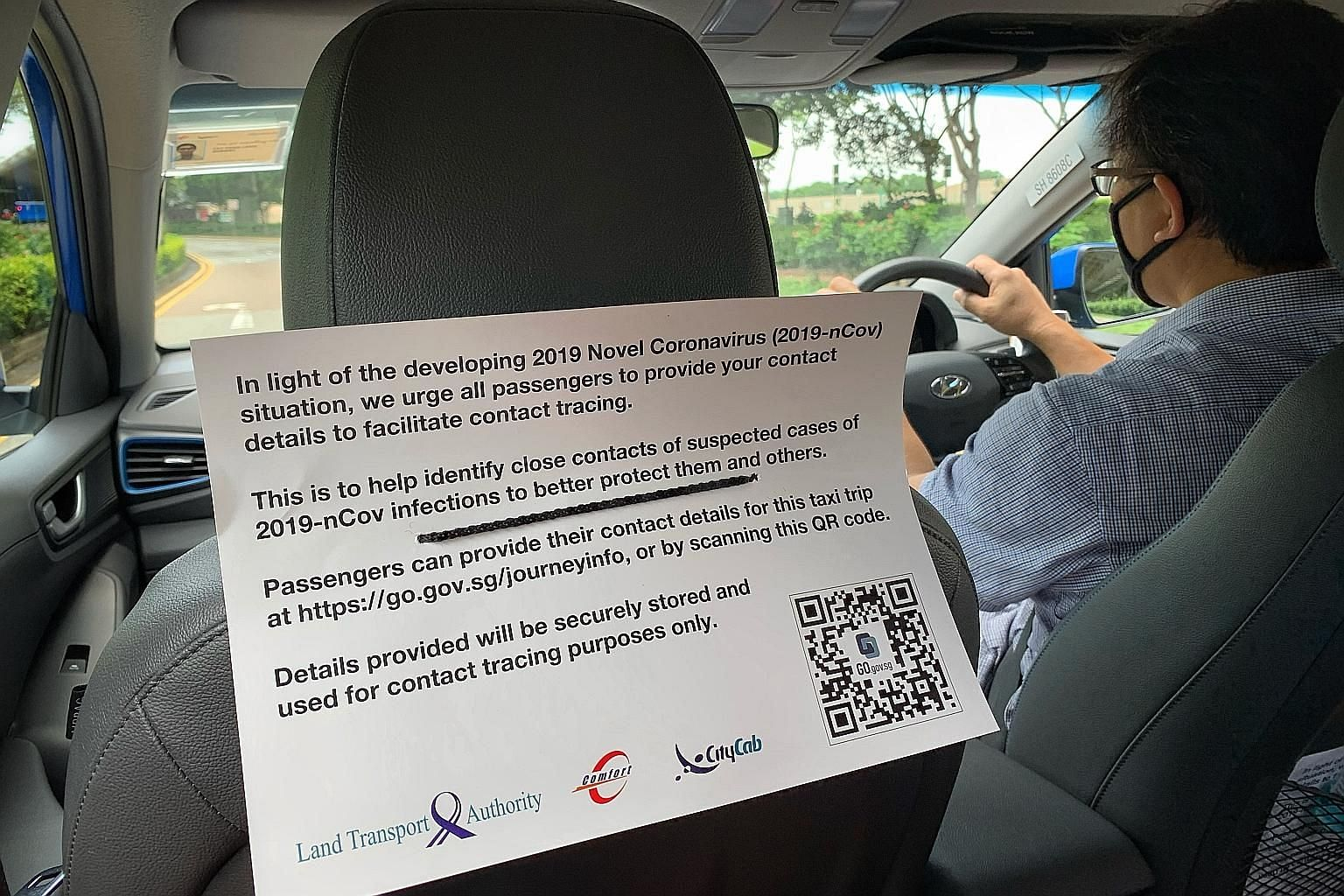 A notice in a ComfortDelGro taxi yesterday asking passengers to provide their contact details for the trip. All cabs will eventually have the QR codes, which are being rolled out across the industry from today. ST PHOTO: ARIFFIN JAMAR