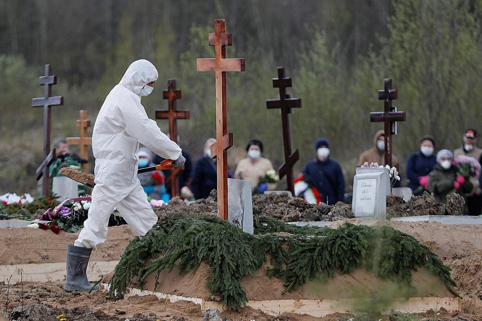 A gravedigger wearing personal protective equipment yesterday in St Petersburg while burying a person who is presumed to have died from Covid-19, with mourners in masks standing at a distance. Russia has almost 250,000 confirmed coronavirus cases, bu