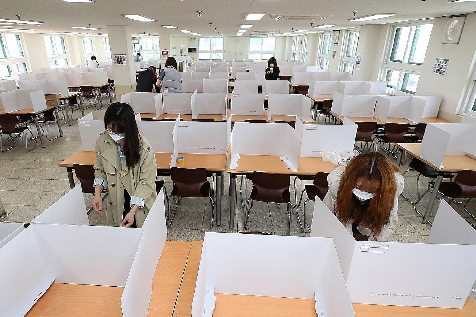 Teachers setting up dividers on tables in a cafeteria at the Duksoo High School in Seoul yesterday to get the school ready for reopening next Wednesday. Incheon city is on high alert for mass infections, after a 25-year-old teacher and resident was f