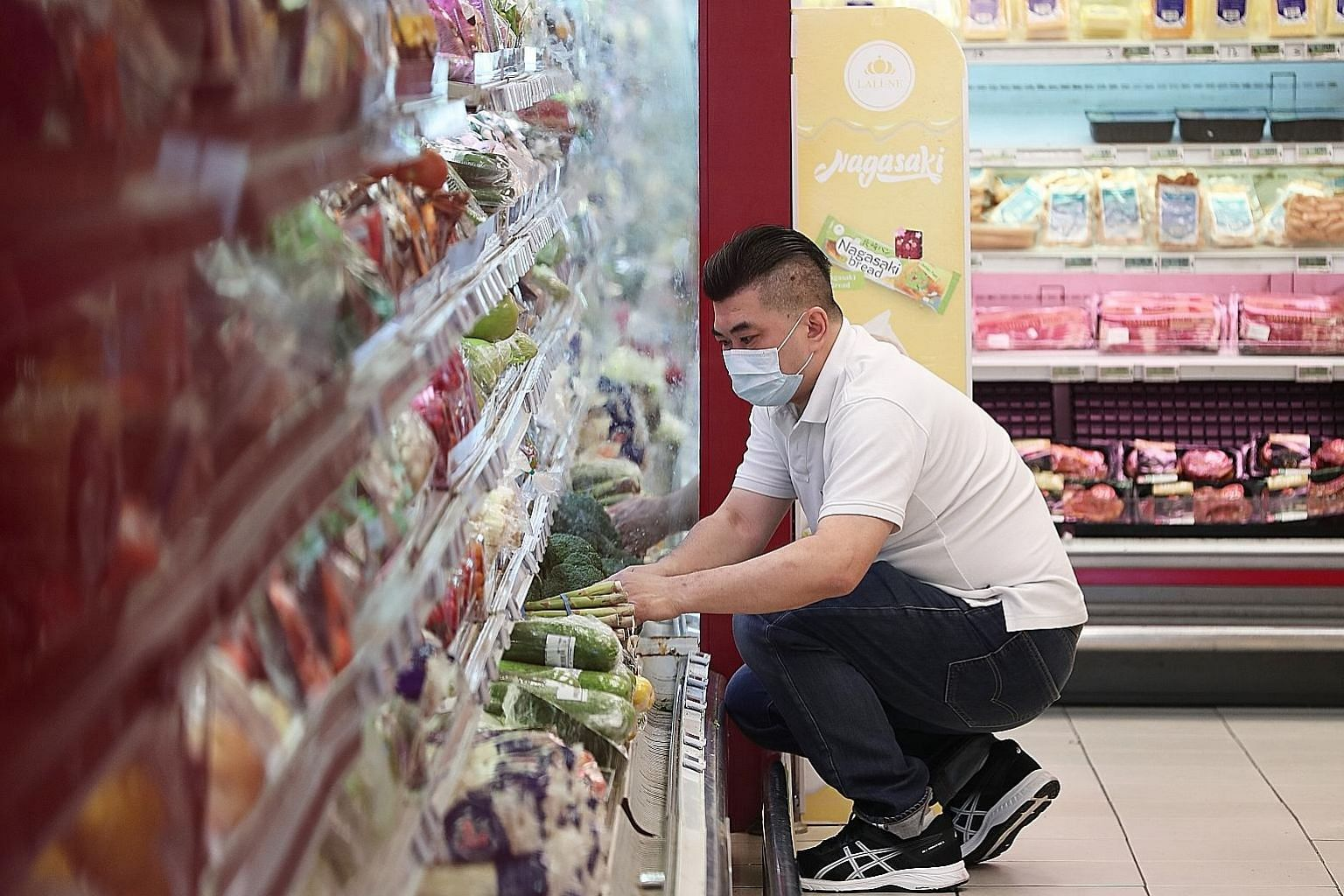 Mr Alex Yeo, a sous-chef at Jiang-Nan Chun at Four Seasons Hotel Singapore, stocking shelves at Cold Storage at The Rail Mall. He is among more than 150 staff from seven hotels who have been redeployed to stores under the Dairy Farm Group. ST PHOTO: