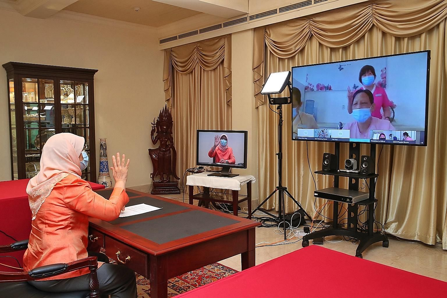President Halimah Yacob chatting with residents and care staff of the Singapore Christian Home via videoconferencing yesterday. Speaking to the media later, she noted that the care staff have put in tremendous effort for the residents, and sacrificed