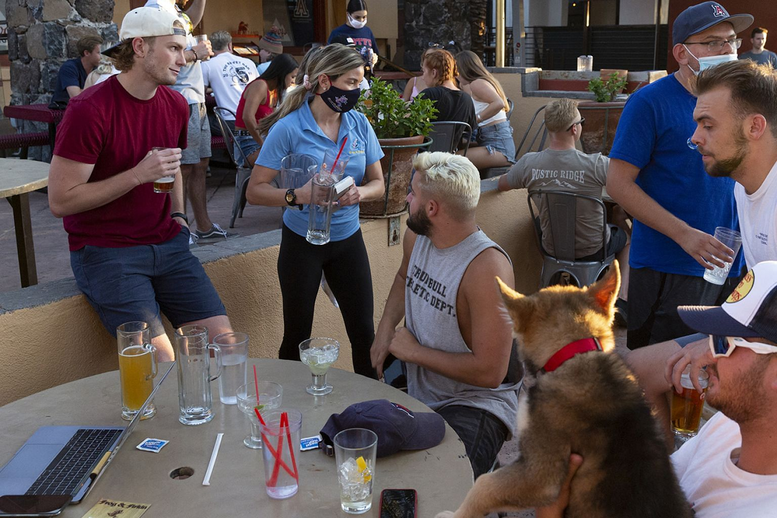 """An employee with a mask serving drinks to customers in a restaurant in Tucson, Arizona. Is eating out """"throwing money away""""? Author Ramit Sethi says: """"It's the same if I pay rent and I enjoy where I live. I'm paying for value."""""""