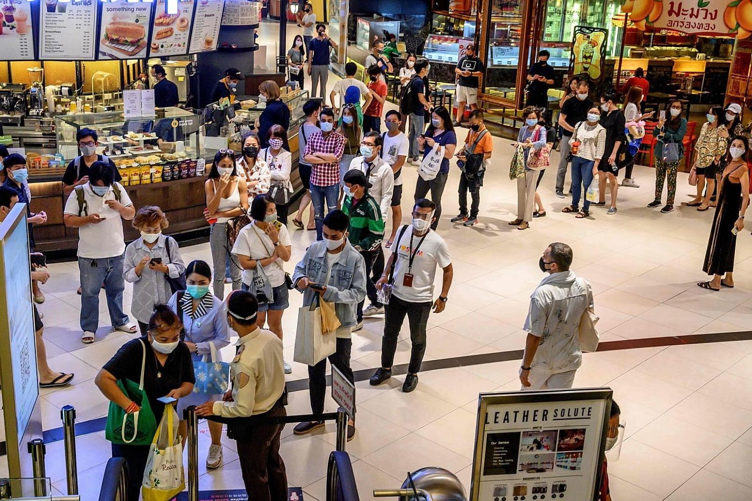 People waiting to enter Siam Paragon in Bangkok on Sunday, the first day Thailand's malls reopened after they were closed in March. With the pandemic hitting domestic activity and tourism, the state planning agency now forecasts a contraction of 5 pe