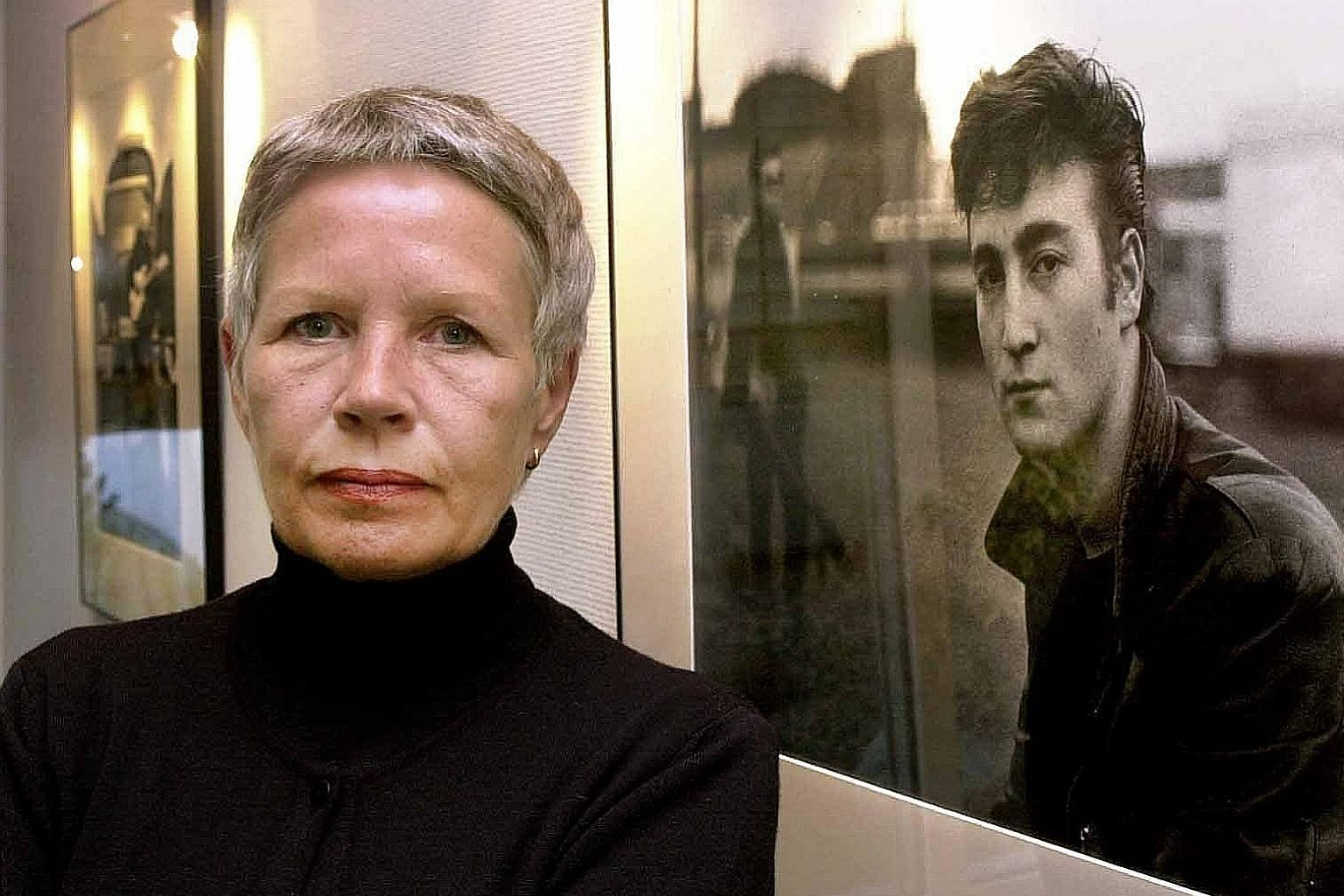 German photographer Astrid Kirchherr (in a 2000 file photo, in Itzehoe, Germany) in front of one of her photos featuring former Beatle John Lennon.