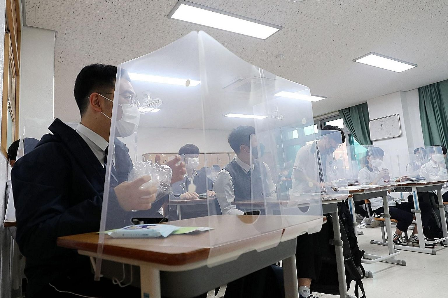 Above: High school seniors sitting behind protective shields as a preventative measure against the coronavirus in a classroom in Daejeon, South Korea, yesterday. Below: Some seniors standing in line to enter the cafeteria as high schools nationwide r