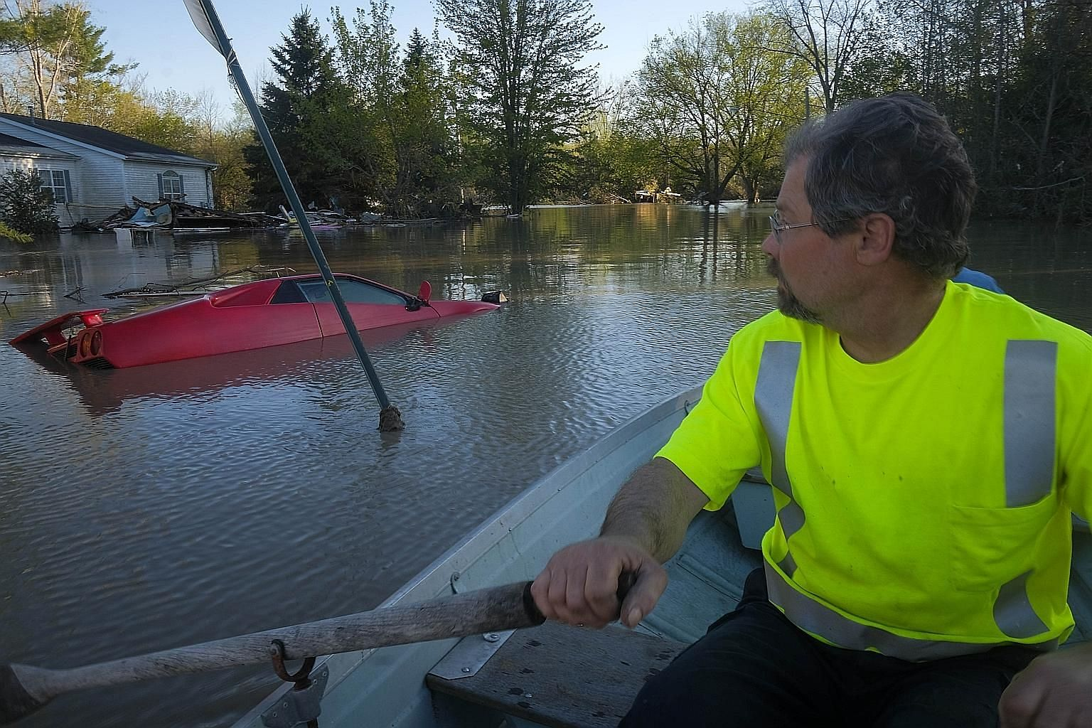 A resident of Sanford village in Midland inspecting the damage in his neighbourhood after floodwaters released by two dam failures submerged parts of the central Michigan town on Wednesday.