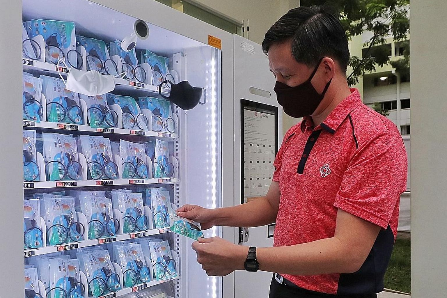Trade and Industry Minister Chan Chun Sing holding a mask from a vending machine at Pek Kio Community Centre yesterday. About 400 of these machines will be placed at all community clubs for those who are unable to pick up their free masks from collec