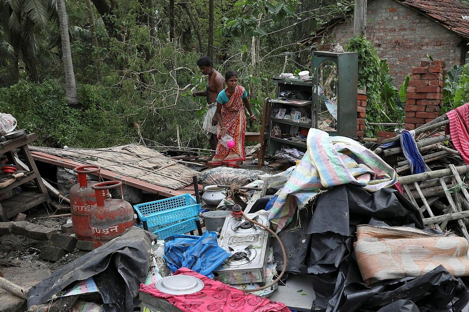 Residents salvaging their belongings from the rubble of a damaged house in the aftermath of Cyclone Amphan in West Bengal, India, yesterday.