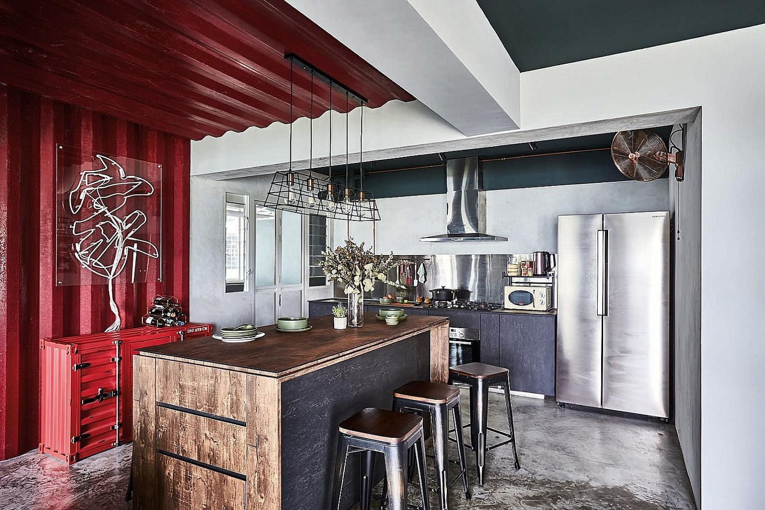 The home owners opted for a green study wall because they love plants and greenery. Corrugated galvanised iron sheets create striking backdrops in the kitchen (above) and living room, while an armchair made from aeroplane fuselage complements the industri