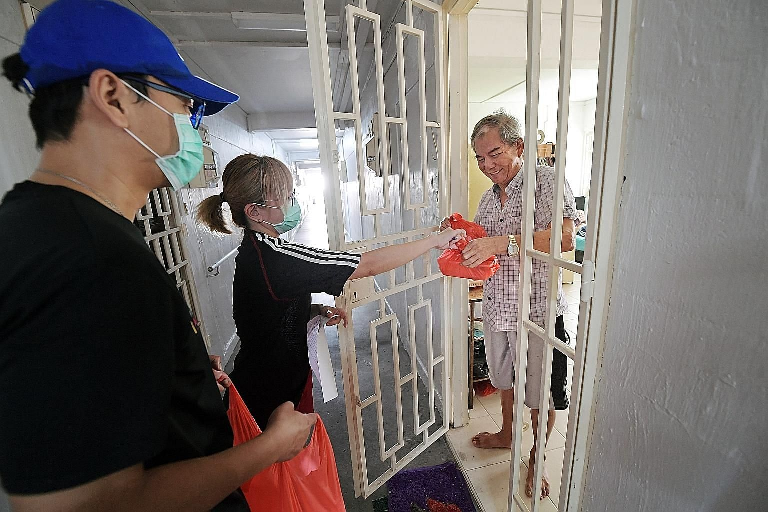 Volunteers Joel Tan, 44, and Gracia Yap, 45, delivering food to Mr Lim Chin Kiat, an elderly resident in Ang Mo Kio earlier this month. The Health Ministry noted that the prolonged suspension of services may cause seniors with little or no social sup