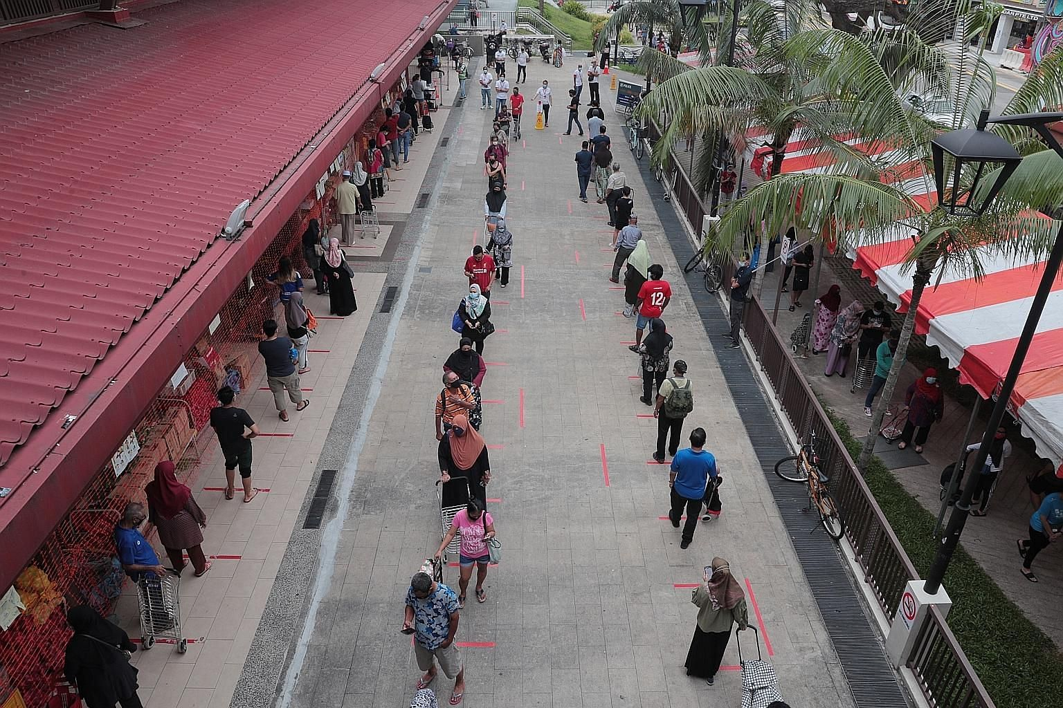A long queue formed outside Geylang Serai Market yesterday as shoppers waited to enter the popular wet market ahead of Hari Raya Aidilfitri celebrations tomorrow. The queue spilled over to the pedestrian walkways as people lined up to purchase necess