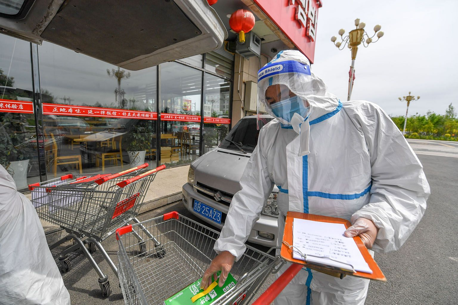 A supermarket employee checking delivery orders in Shulan, Jilin province, on Wednesday. Residential districts with confirmed and suspected cases are completely locked down and daily supplies are delivered to residents. One of the first reported clus